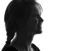 Black and white portrait of a profile of face of a young joyful woman passing emotional inspiration with pigtails on a white isolated background