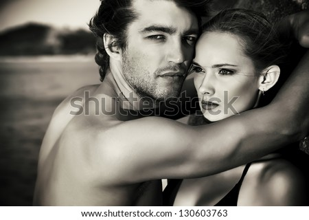 Black-and-white portrait of a sexual young couple in love having holidays on the sea.