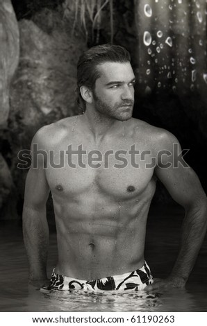 Black and white portrait of a sexy shirtless man against exotic outdoor background