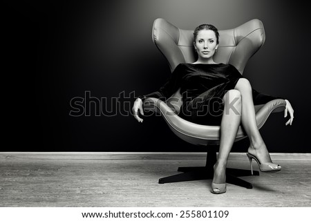 Black-and-white portrait of a stunning fashionable model sitting in a chair in Art Nouveau style. Business, elegant businesswoman. Interior, furniture. #255801109