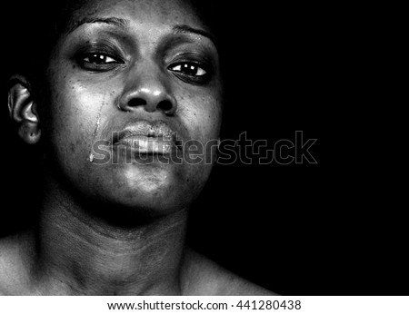 Black and white portrait of a tearful African-American woman posing against a black background