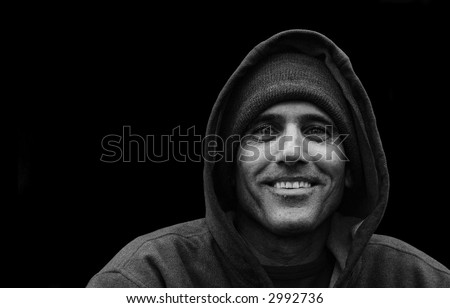 black and white portrait of a urban man wearing jacket with hood smiling on black background