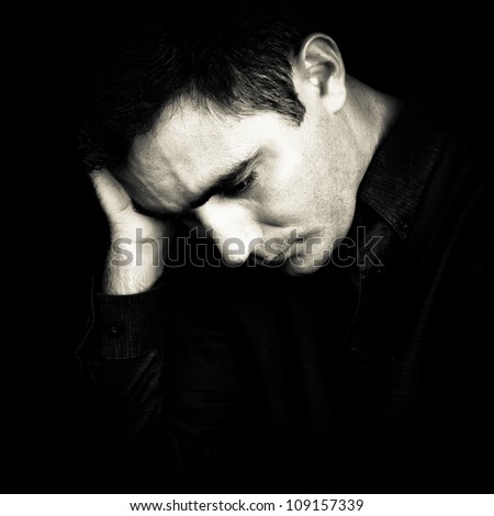 Black and white portrait of a worried and depressed man isolated on black