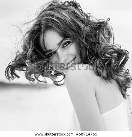 Black and white portrait of a young beautiful woman. Woman in Black & White. Black and white portrait of smile woman. Close-up. Black white photography.  Autumn portrait on the beach.