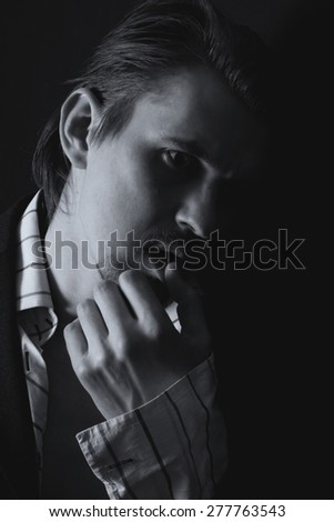 Black and white portrait of a young man on a black background