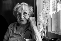 Black-and-white portrait of an elderly woman in her home.