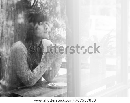 Black and white portrait of Asian woman alone in coffee shop with rainy drops on rainy day for copy space