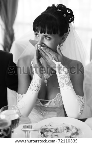 Black and white portrait of beautiful bride. Crying. Siting at the table