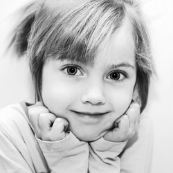 Black and white portrait of beautiful funny little girl. Selective focus on the eyes of a child. Retro style.