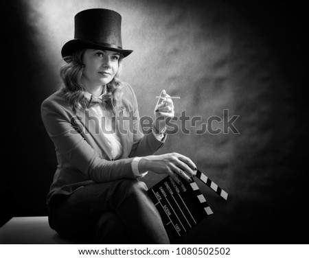 Black and white portrait of beautiful woman in a cylinder, a jacket and a bow tie with cigarette and clapperboard isolated on dark background. Bnw movie concept #1080502502
