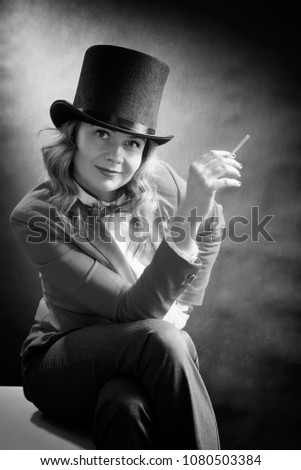 Black and white portrait of beautiful woman in a cylinder, a jacket and a bow tie with cigarette isolated on dark background. Bnw movie concept #1080503384