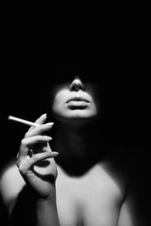 black and white portrait of Beautiful woman in a hat and with a cigarette. Retro style portrait. Lady Girl with face under Shadow