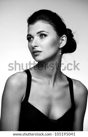 Black and white portrait of beautiful woman  in black dress on natural background