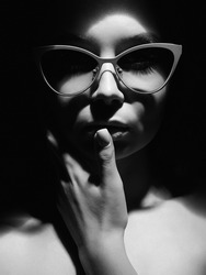 Black and white portrait of Beautiful woman in glasses. Retro style portrait. Lady Girl looking from the dark