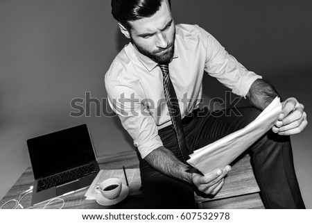 black and white portrait of businessman sitting on table and reading documents