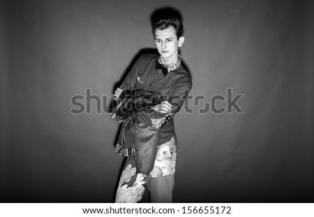 Black and white portrait of fashionable man posing against black background
