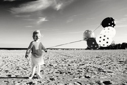 Black and white portrait of funny Caucasian child kid with large bunch of balloons. Baby playing smiling on beach at sunset. Happy lifestyle childhood concept
