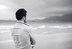 Black and white portrait of handsome young Caucasian man walking alone on the beach