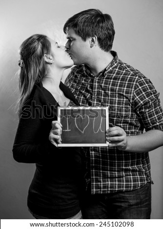Black and white portrait of kissing couple in love holding \