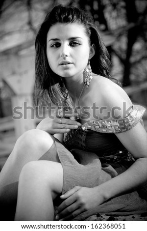 Black and white portrait of sad woman in dress sitting outdoor