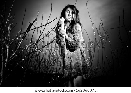 Black and white portrait of sad woman posing against sky and trees