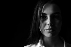Black and white portrait of scared female victim on dark background. Concept of violence