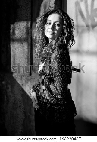 Black and white portrait of sexy curly woman in blouse posing against wall on street