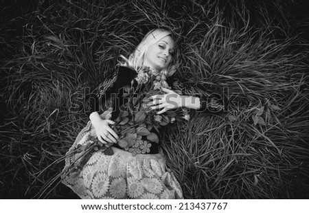 Black and white portrait of sexy woman with roses lying on field