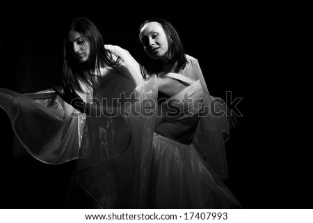 Black-and-white portrait of two girls in white raiment dancing in semidarkness