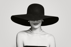 Black and white portrait of vintage woman in classic hat and pearls jewelry, retro styling girl