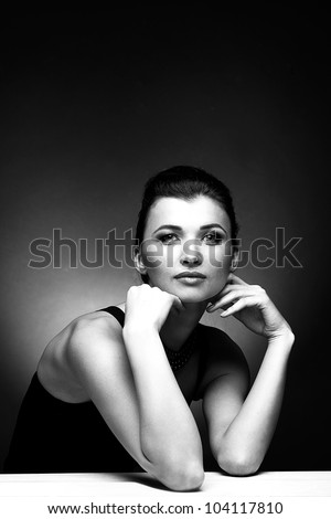 Black and white portrait of woman in black dress on natural background