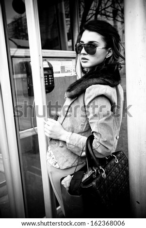 Black and white portrait of woman in sunglasses standing in payphone cabin