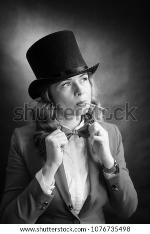 Black and white portrait of young beautiful woman in a cylinder, a jacket and a bow tie with cigarette isolated on dark background. Retro movie concept #1076735498