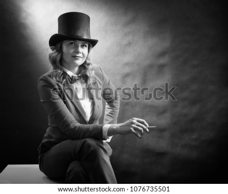 Black and white portrait of young beautiful woman in a cylinder, a jacket and a bow tie with cigarette isolated on dark background. Retro movie concept #1076735501