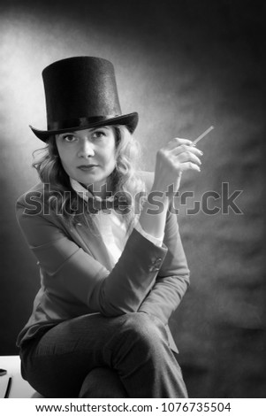 Black and white portrait of young beautiful woman in a cylinder, a jacket and a bow tie with cigarette isolated on dark background. Retro movie concept #1076735504