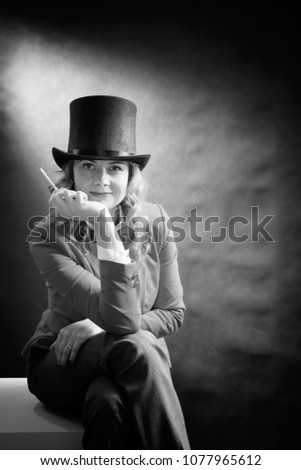 Black and white portrait of young beautiful woman in a cylinder, a jacket and a bow tie with cigarette isolated on dark background. Bnw movie concept #1077965612