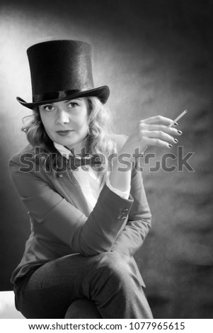 Black and white portrait of young beautiful woman in a cylinder, a jacket and a bow tie with cigarette isolated on dark background. Bnw movie concept #1077965615