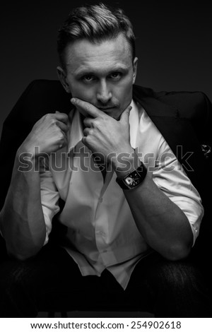 Black and white portrait of young business man in a suit on dark black background.