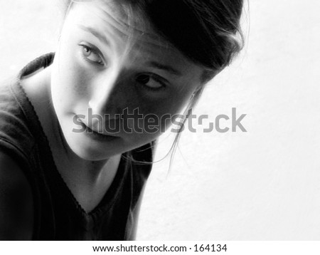 Black and white portrait of young girl looking over shoulder