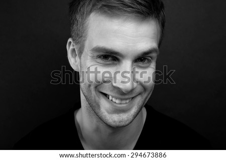 Black and white portrait photo of young happy man with a blinding smile in v neck t shirt