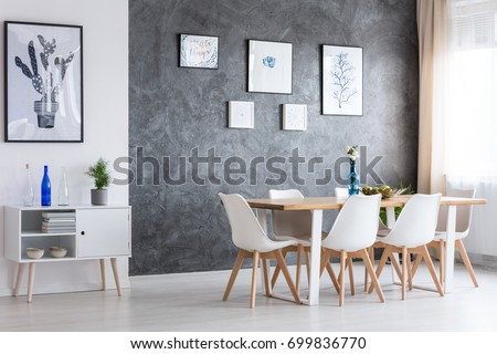 Black and white poster on white wall above white cupboard in classic dining room #699836770