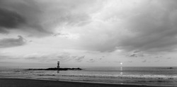 Black and white process style of lighthouse in small rock island with sunset and clouds sky in background. Taken at Khao Lak beach, Pangnga south of Thailand.