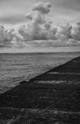 Black and White Profile of Ocean and Stormy Sky.   Monochrome view of a cement pier and Waikiki Bay with room for copy.
