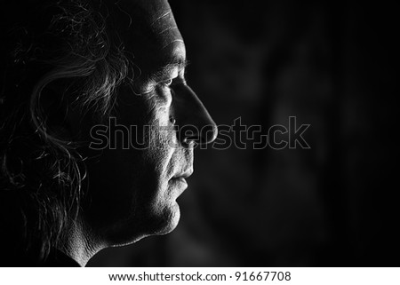 Black and white profile portrait of older white male with side lighting.