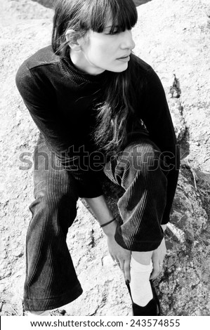Black and white profile portrait of pretty stylish young woman outdoors wearing black turtle-neck, boyish pants, pulling up her socks, looking aside. High key portrait, harsh sun light, copy space