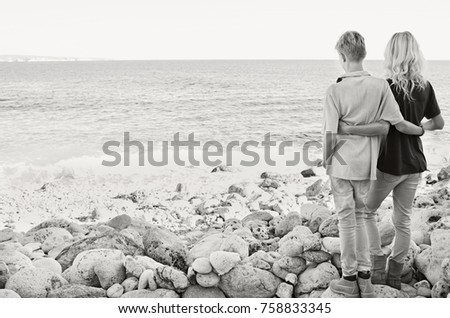 Black and white rear view of mother and son on destination rocky beach together contemplating the sea hugging on travel holiday, closeness family sharing love outdoors. Recreation discovery lifestyle.