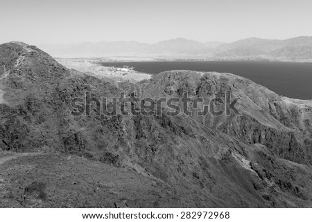 Black and white Red sea mountains and Eilat Aqaba cities view, harbor seaport, Israel.