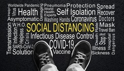 Black and white rendering of person standing over highlighted Social Distancing word cloud. Concept of social distancing measure to control worldwide COVID-19 coronavirus pandemic.