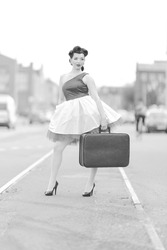 Black and white retro style photo. A girl in a dress and hairstyle in the style of the 40-50s on a city street on tram tracks on a sunny day