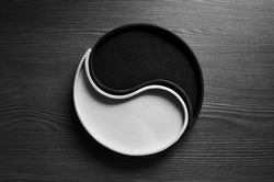 Black and white Sand Ying Yang Symbol on a wood table
